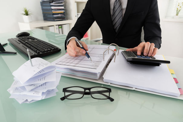54191004 – close-up of businessman calculating tax in office